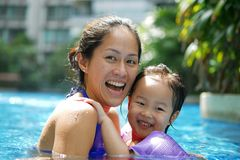 Asian Chinese Mother and Daughter smiling and bonding in the swimming pool smiling happy stock photography