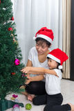 Asian Chinese mother and daughter decorating Christmas tree at h Stock Images