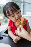 Asian Chinese mother and daughter eating fried chicken Royalty Free Stock Images