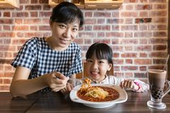 Asian Chinese mother and daughter eating spaghetti bolognese Royalty Free Stock Photos