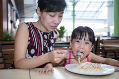 Asian Chinese mother and daughter eating spaghetti bolognese. At outdoor cafe Royalty Free Stock Images