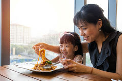 Asian Chinese mother and daughter eating spaghetti bolognese Royalty Free Stock Image