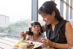 Asian Chinese mother and daughter eating steak Stock Photo