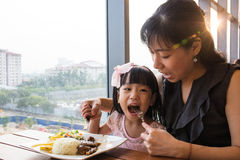 Asian Chinese mother and daughter eating steak Royalty Free Stock Photo