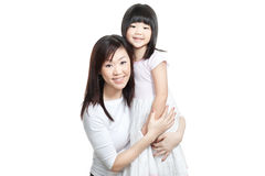 Asian Chinese mother and daughter family portrait. Chinese young mother and daughter both with long hair hugging one another for a family portrait Stock Photo