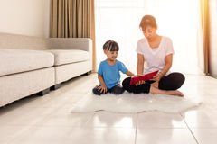 Asian Chinese mother and daughter reading on the floor Stock Photography