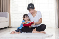 Asian Chinese mother and daughter reading on the floor Stock Image