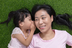 Asian Chinese mother and daughter whispering and gossiping Royalty Free Stock Photos