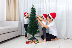Asian Chinese mother and daughters decorating Christmas tree at Stock Images