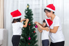 Asian Chinese mother and daughters decorating Christmas tree at Royalty Free Stock Images