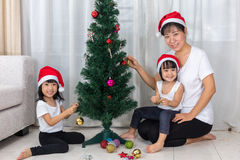 Asian Chinese mother and daughters decorating Christmas tree at Royalty Free Stock Photography