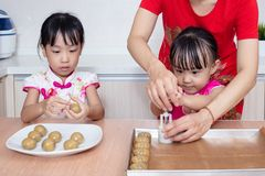 Asian Chinese mother and daughters making moon cake in the kitchen. At home stock photos