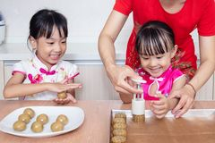 Asian Chinese mother and daughters making moon cake in the kitchen. At home stock photography