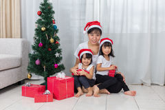 Asian Chinese mother and daughters sitting next to Christmas tre Stock Image