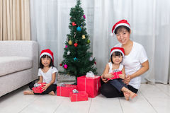 Asian Chinese mother and daughters sitting next to Christmas tre Royalty Free Stock Photo