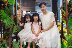 Asian Chinese mother and daughters sitting on a swing Stock Images