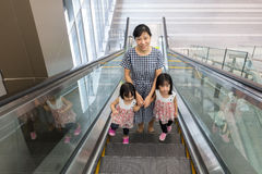 Asian Chinese mother and daughters taking escalator at MRT Stati Stock Images