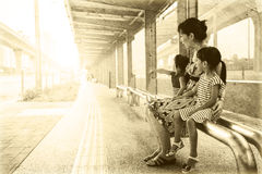 Asian Chinese mother and daughters waiting for a bus Stock Photography