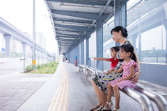 Asian Chinese mother and daughters waiting for a bus Royalty Free Stock Image
