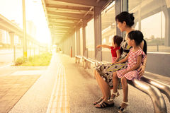 Asian Chinese mother and daughters waiting for a bus Royalty Free Stock Photos