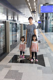 Asian Chinese mother and daughters waiting for transit at statio Royalty Free Stock Photos