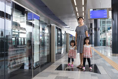 Asian Chinese mother and daughters waiting for transit at statio Royalty Free Stock Images