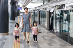 Asian Chinese mother and daughters waiting for transit at statio Stock Images