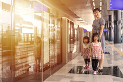 Asian Chinese mother and daughters waiting for transit at statio Royalty Free Stock Photography