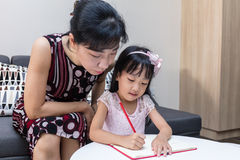 Asian Chinese mother teaching daughter doing homework. At home royalty free stock images