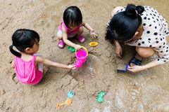 Asian Chinese mum and daughter playing sand together Stock Photos