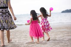Asian Chinese mum and daughters playing sand together. At beach outdoor stock photos