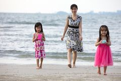 Asian Chinese mum and daughters playing sand together. At beach outdoor royalty free stock photography