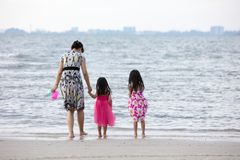 Asian Chinese mum and daughters playing sand together. At beach outdoor royalty free stock images