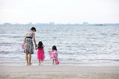 Asian Chinese mum and daughters playing sand together. At beach outdoor stock images