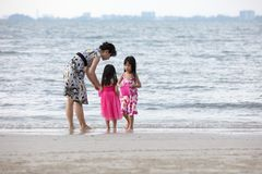 Asian Chinese mum and daughters playing sand together. At beach outdoor royalty free stock photos