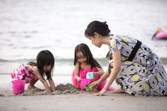 Asian Chinese mum and daughters playing sand together. At beach outdoor royalty free stock image