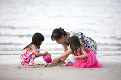 Asian Chinese mum and daughters playing sand together. At beach outdoor stock image