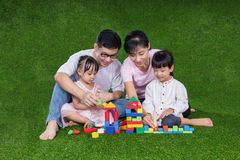 Asian Chinese parents and daughters playing blocks on the grass Stock Photo