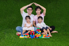 Asian Chinese parents and daughters playing blocks on the grass Royalty Free Stock Photos