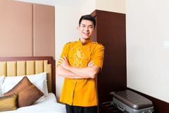 Asian Chinese porter bringing suitcase to luxury hotel room royalty free stock photography