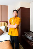 Asian Chinese porter bringing suitcase to luxury hotel room. Asian Chinese baggage porter or bell boy or page bringing the suitcase of guests to the luxury hotel Stock Photo