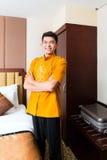 Asian Chinese porter bringing suitcase to luxury hotel room stock photo