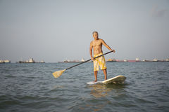Asian chinese retire surfing in the sea Stock Photos
