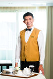 Asian Chinese room service waiter serving food in hotel Stock Photos