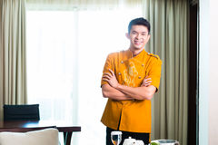 Asian Chinese room service waiter serving food in hotel suite stock photography