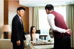 Asian Chinese room waiter serving food in hotel suite royalty free stock images