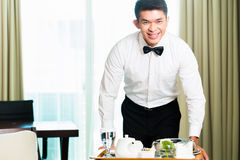 Asian Chinese room waiter serving guests food in hotel. Asian Chinese room service waiter or steward serving guests food in a grand or luxury hotel room Royalty Free Stock Photo