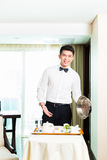 Asian Chinese room waiter serving guests food in hotel. Asian Chinese room service waiter or steward serving guests food in a grand or luxury hotel room Royalty Free Stock Photos