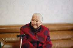 Asian Chinese 90s old woman on her grandson`s wedding day. Sad and lonely Asian Chinese old woman, 93 years old, up to 90s , silvery hair, golden earing on her Royalty Free Stock Photos