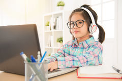 Asian chinese schoolgirl study with computer. Net website and wearing headsets listen foreign music. sweet kid thinking typing something stock photos